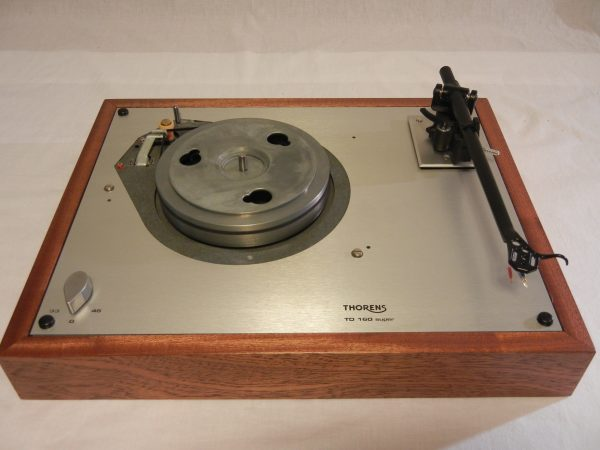 "After the reproduction plate is carefully attached with contact cement, the turntable mechanism is mounted in a 3/4"" solid wood plinth (African Sipo, in this case)"